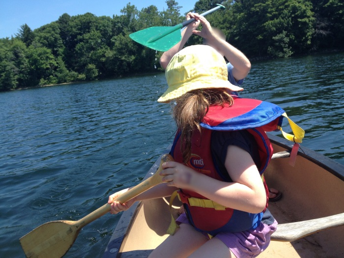 child canoeing and holding a canoe paddle